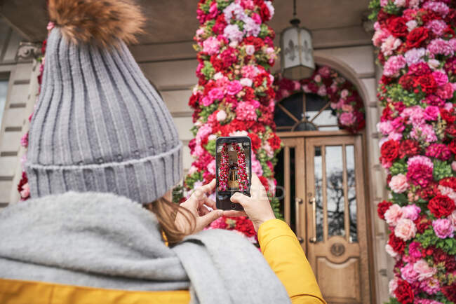 Back view of unrecognizable female in outerwear using smartphone to take photo of beautiful floral decorations outside elegant estate — Stock Photo