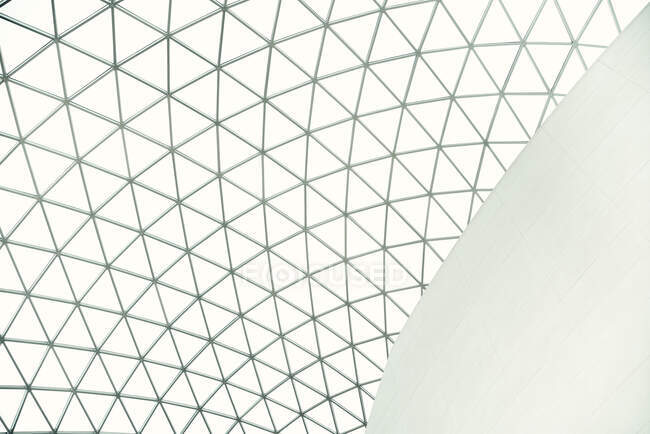 From below geometric dome ceiling of with many triangular parts inside of white futuristic building in city — Stock Photo