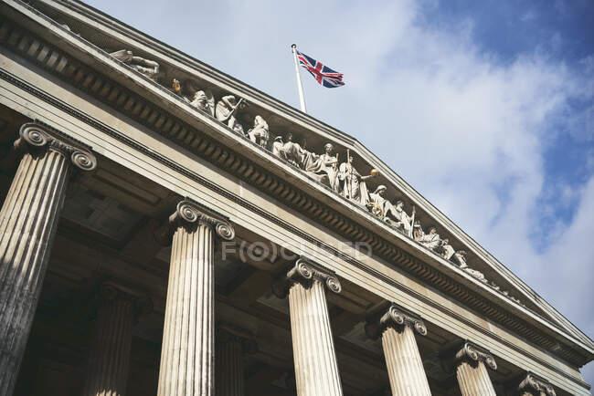 Da sotto bandiera della Gran Bretagna sventola sulla cima di un vecchio edificio ornamentale con colonne contro il cielo nuvoloso — Foto stock