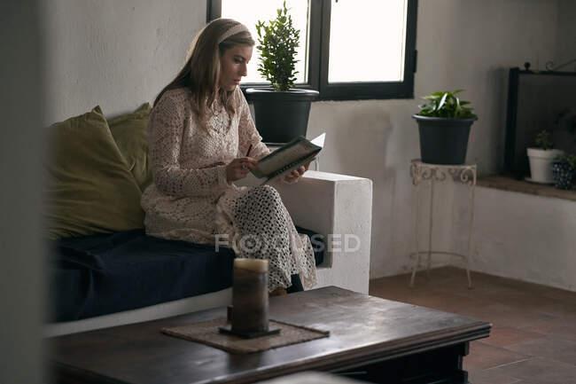 Зосереджена жінка робить нотатки в зошиті на дивані вдома. — стокове фото
