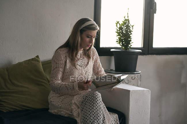 Focused signora prendere appunti in notebook sul divano a casa — Foto stock