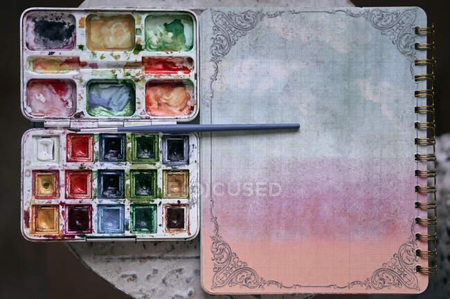Верхний вид красочной палитры с акварелью на столе возле красочного листа ноутбука на столе — стоковое фото