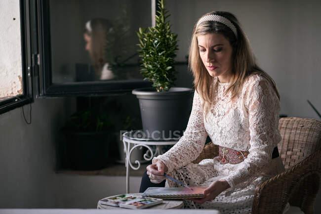 Мирна жінка малює в щоденнику сидячи на стільці. — стокове фото