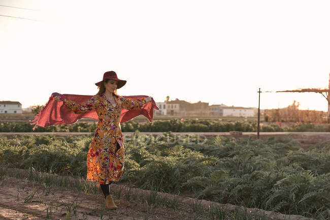 Charming young woman in colorful light dress and hat walking on passage of plantations with pink headscarf oh back in countryside — Stock Photo