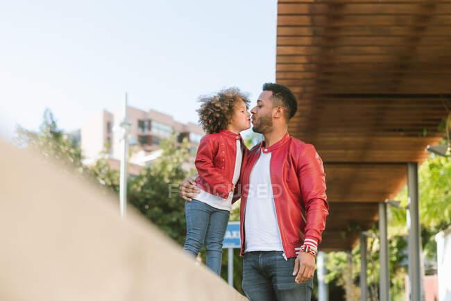 Счастливый молодой этнический мужчина и милая маленькая кудрявая дочь в похожих кожаных куртках и джинсах обнимаются и целуются, стоя вместе на городской улице — стоковое фото