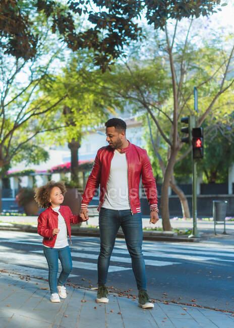 Щасливий молодий етнічний чоловік з маленькою донькою, одягненою в такий самий одяг, тримаючись за руки, ходячи вулицею міста в сонячний день. — стокове фото