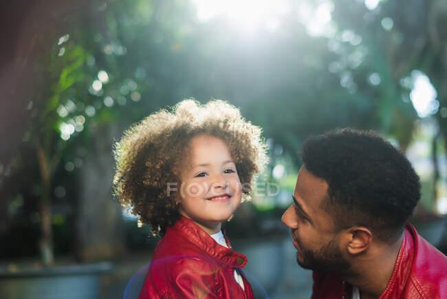 Вид сбоку на очаровательную жизнерадостную этническую девушку, обнимающую счастливого отца в похожей кожаной куртке, отдыхающую вместе в парке в солнечный день — стоковое фото