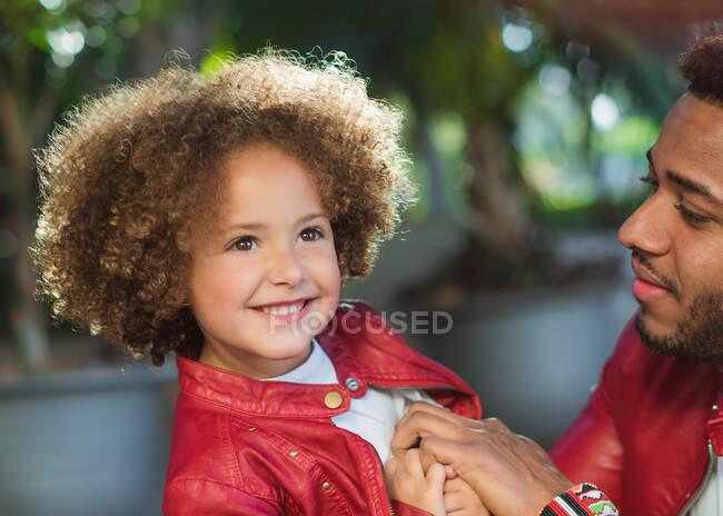 Vista lateral de adorable chica étnica alegre con padre feliz con chaqueta de cuero similar mientras descansan juntos en el parque en el día soleado - foto de stock