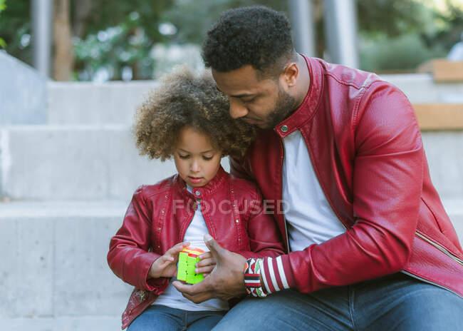 Junger ethnischer Vater mit süßer Tochter in ähnlichem Outfit sitzt auf Treppen und spielt Rubik Cube, während er den Tag zusammen in der Stadt verbringt — Stockfoto