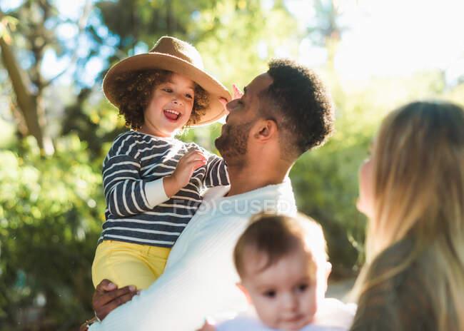 Alegre joven familia multirracial con niños pequeños disfrutando del tiempo juntos mientras descansan en el parque verde en el soleado día de verano - foto de stock