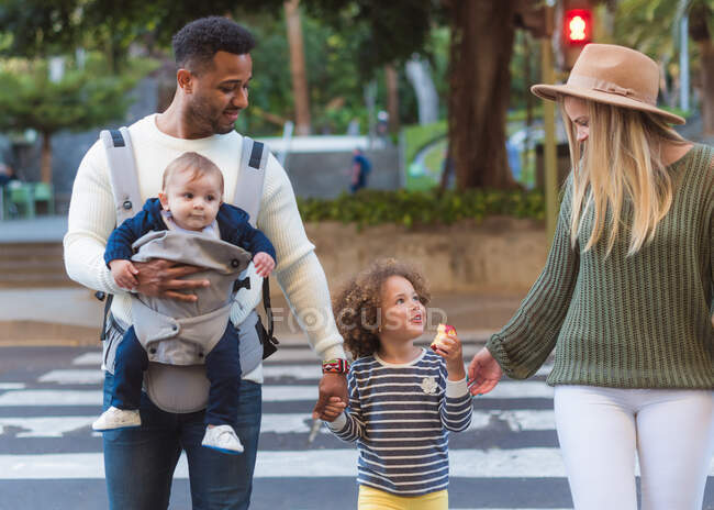 Happy young multiracial parents with little daughter eating apple and cute infant boy crossing road on zebra while walking in city in summer day — Stock Photo
