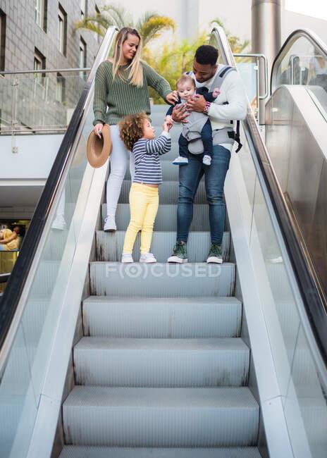Снизу счастливая многорасовая семья, спускающаяся по эскалатору, и маленькая девочка, ухаживающая за маленьким братом, которого несет папа, проводя вместе летний день в городе — стоковое фото