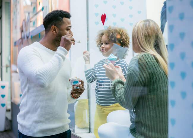 Любить многонационального мужчину и женщину с очаровательной дочерью, играющей во время мороженого в городском кафе — стоковое фото