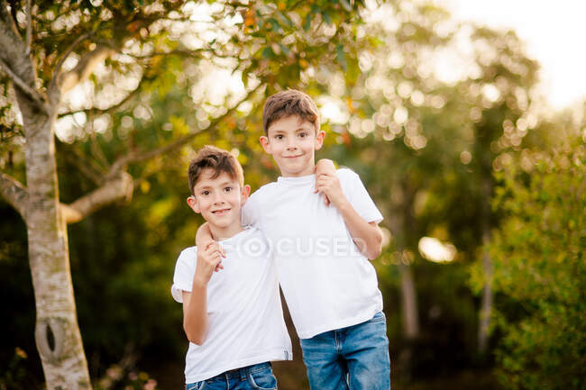 Sonrientes hermanos gemelos en camisetas blancas y jeans abrazando y mirando a la cámara mientras están de pie en el parque verde en el día de verano - foto de stock