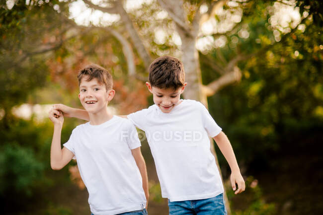 Happy twin boys hugging and looking at camera in park — Stock Photo
