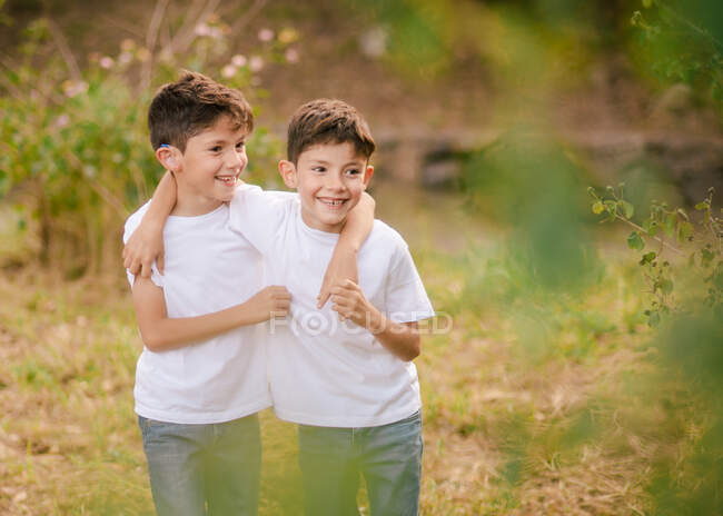 Happy twin boys hugging and looking away in park — Stock Photo