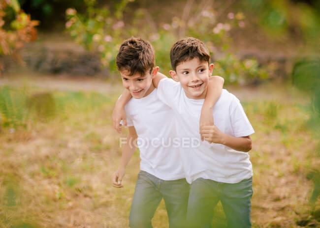 Felice gemelli abbracciare e guardare lontano nel parco — Foto stock