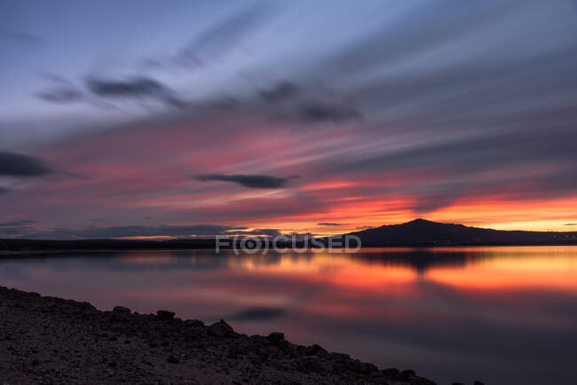 Long exposure picturesque view of cloudy sundown sky over mountain and peaceful lake water in nature — Stock Photo