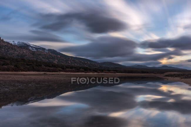 Longue exposition vue pittoresque du ciel nuageux au coucher du soleil sur la montagne et l'eau paisible du lac dans la nature — Photo de stock