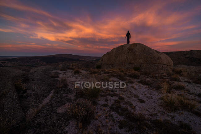 Silhouette of unrecognizable explorer standing on boulder against cloudy sundown sky during trip in mountainous terrain — Stock Photo