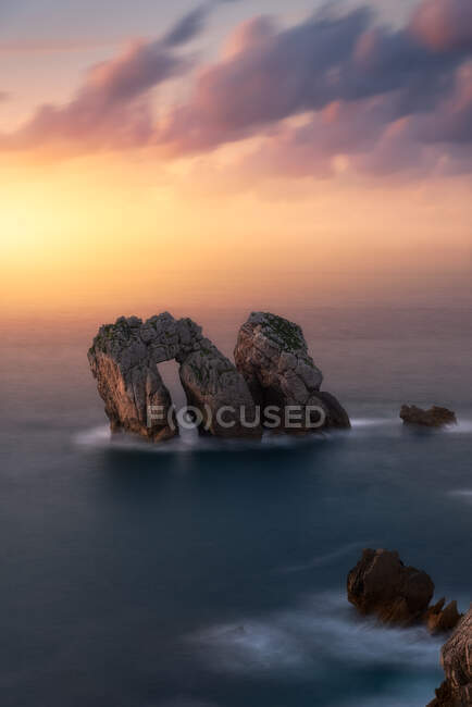 From above of rough rocks among calm blue sea under colorful evening sunset cloudy sky — Stock Photo