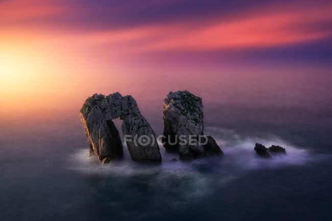 Над грубими скелями серед спокійного блакитного моря під яскравим вечірнім заходом хмарного неба. — стокове фото