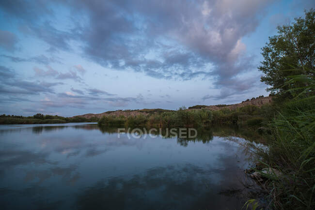 Grassy shore of calm pond against cloudy sky in countryside — Stock Photo
