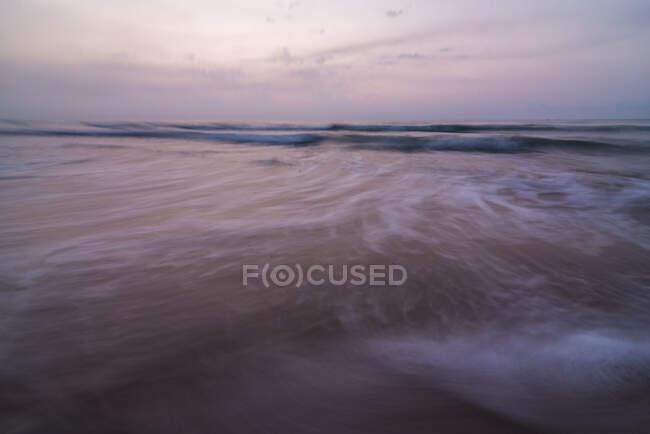 Les vagues de la mer roulant sur la côte sablonneuse humide contre ciel nuageux en soirée dans la nature — Photo de stock