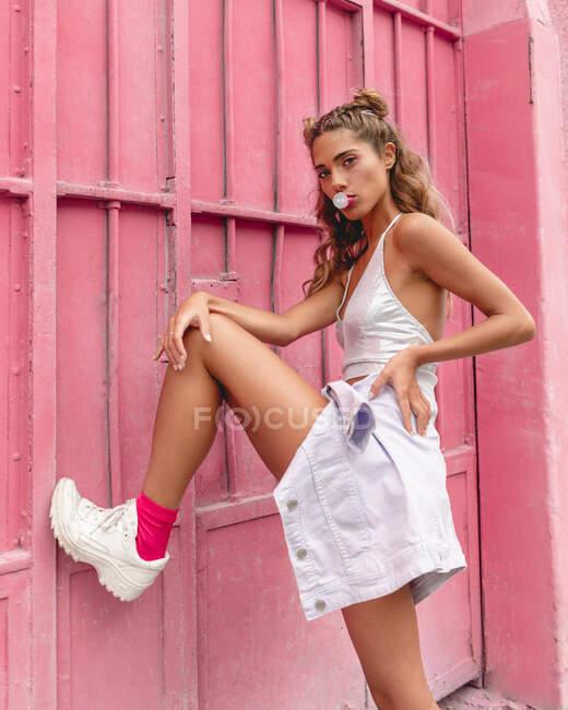 Vista lateral de glam fresco hembra delgada en traje elegante poner pierna en la pared de color rosa y soplado de goma de mascar mirando a la cámara en la calle de la ciudad moderna - foto de stock