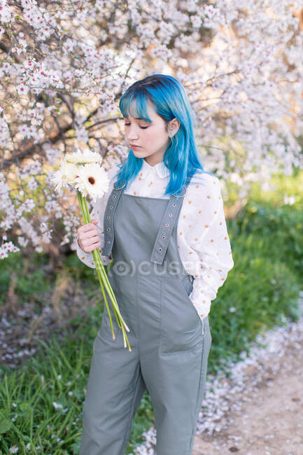 Modern trendy female with blue hair holding and looking at bouquet of fresh flowers while standing in blooming spring garden — Stock Photo
