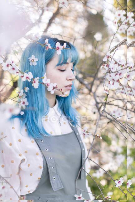 Giovane femmina elegante con lunghi capelli blu con gli occhi chiusi che indossano tendenza generale godendo profumo di albero in fiore mentre in piedi in giardino primaverile — Foto stock