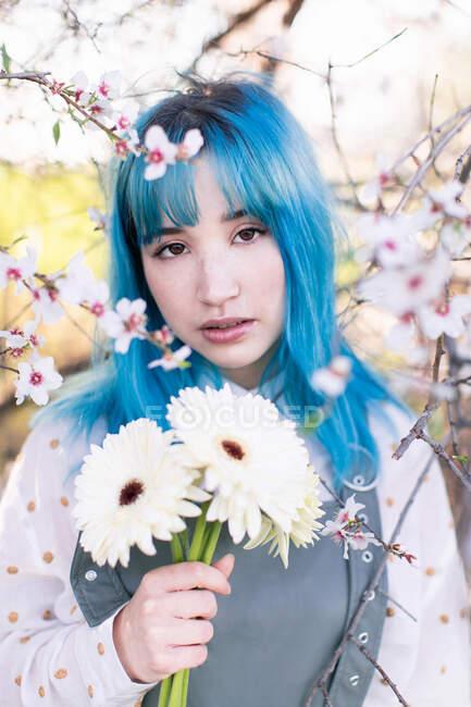 Moderna hembra de moda con cabello azul sosteniendo ramo de flores frescas y mirando a la cámara mientras está de pie en el floreciente jardín de primavera - foto de stock