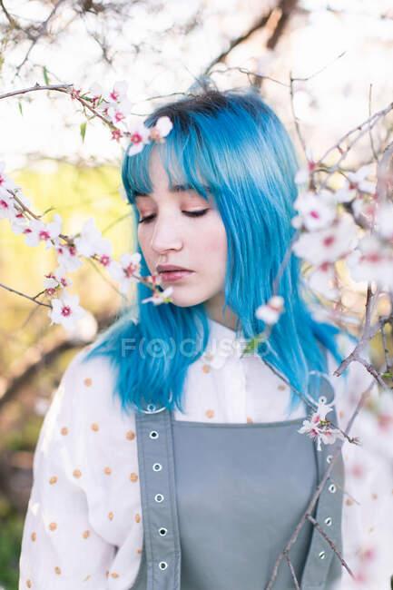 Joven mujer elegante con el pelo largo y azul con los ojos cerrados usando la fragancia general de moda disfrutando de la floración del árbol mientras está de pie en el jardín de primavera - foto de stock