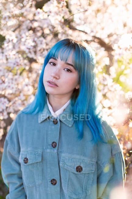 Молодая стильная женщина с длинными голубыми волосами с руками в кармане, смотрящая на камеру, одетая в модный общий вид, наслаждаясь цветущим деревом, стоя в весеннем саду — стоковое фото
