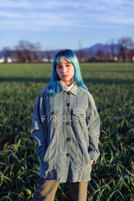 Думлива молода жінка з синім волоссям дивиться на камеру, одягнену в модний піджак, що стоїть на зеленому полі в сонячний вечір. — стокове фото