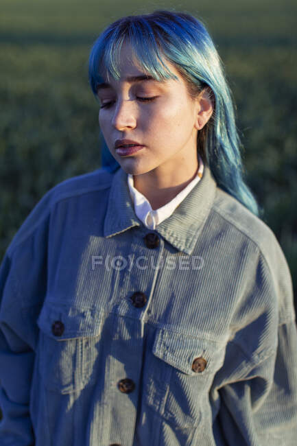 Upset pensive young female with blue hair dressed in trendy jacket standing in green field in sunny evening — Stock Photo
