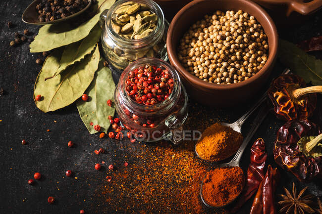 Top view composition with different kinds of natural aromatic spices placed on slate surface background — Stock Photo