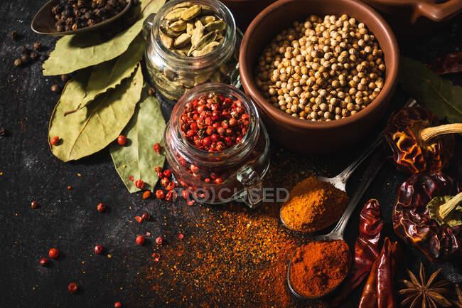 Composition vue de dessus avec différents types d'épices aromatiques naturelles placées sur fond de surface en ardoise — Photo de stock