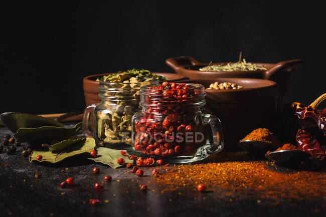 De la composition ci-dessus avec différents types d'épices aromatiques naturelles placées sur fond de surface d'ardoise — Photo de stock