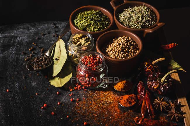 De composición anterior con diferentes tipos de especias aromáticas naturales colocadas en el fondo de la superficie de pizarra - foto de stock