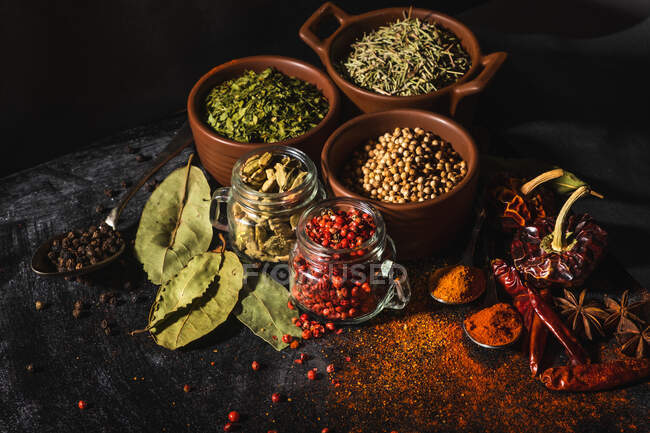 From above composition with different kinds of natural aromatic spices placed on slate surface background — Stock Photo