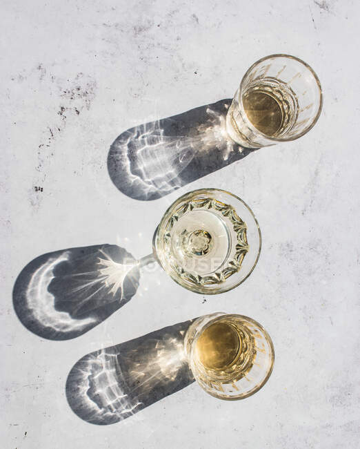 Top view composition of various glasses with alcohol drinks in sunlight leaving shadows and lights on marble surface — Stock Photo