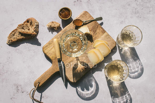 Top view composition with glasses of wine served with sliced cheese and bread with jam on marble table with wooden board in sunlight — Stock Photo