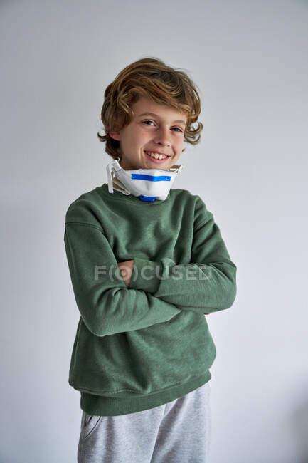 Niño rubio, de unos 8 años, usando un respirador para coinfectarse con un virus - foto de stock