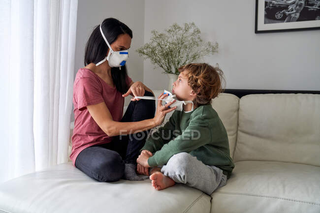 Mother putting on a respirator for her child to avoid possible infection — Stock Photo