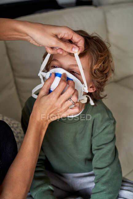 Mãe colocando um respirador para seu filho para evitar possíveis infecções — Fotografia de Stock