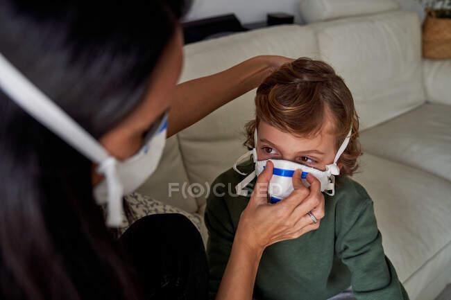 Madre poniéndose un respirador para que su hijo evite una posible infección - foto de stock