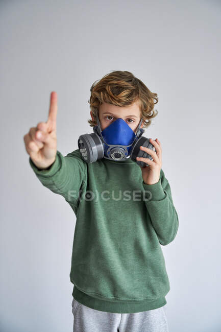 Blond boy, wearing a respirator and showing one finger — Stock Photo