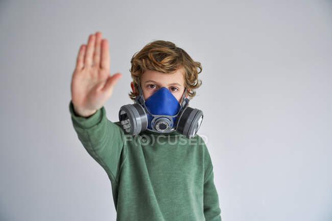 Garçon blond, portant un respirateur et montrant un panneau stop — Photo de stock