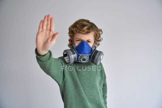 Ragazzo biondo, indossa un respiratore e mostra segno di stop — Foto stock